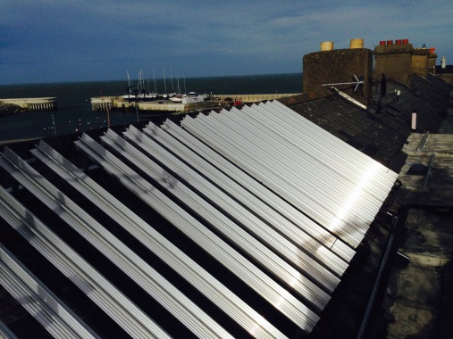 airgo heat pump on a roof beside the sea
